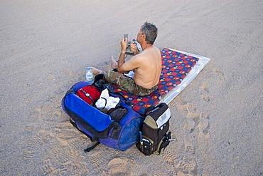 Man shaving his beard in the desert