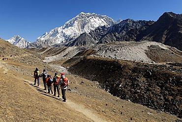 Trekking group on Khumbu glacier with Nuptse (7861), Khumbu Himal, Sagarmatha National Park, Nepal