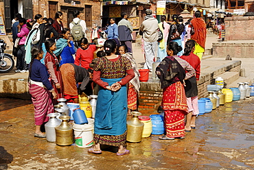 Woman gets drinking water in the old town of Bhaktapur, Kathmandu, Nepal