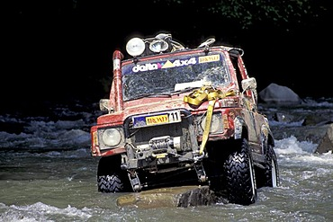Offroad vehicle is standing on a rock in a river
