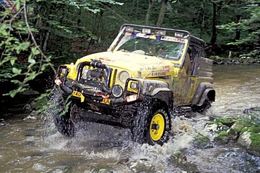 Offroad vehicle is driving in riverbed
