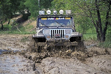 Jeep offroad vehicle are driving with speed through mud