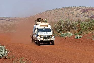 Toyota Landcruiser FJ 75 Arkana safari car with trailer driving on a red road in Karijini National Park Pilbara region western australia WA