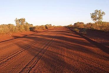 Straight gravel road in Pilbara outback at sunset western australia WA