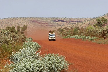 Toyota Landcruiser FJ 75 Arkana safari car driving on a red road in Karijini National Park Pilbara region western australia WA