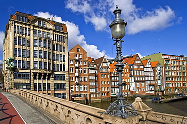 Bridge with ornate lamps leading to Haus der Seefahrt (House of Seafaring) at left beside historic timber-framed merchant houses on the Nikolaifleet in the historic centre of Hamburg, Germany