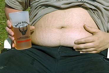 Young man present his beer belly