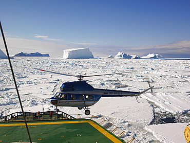 Helicopter landing on Capt. Khlebnikov (icebreaker) after a flight over the icebergs off of Franklin Island, Antarctica