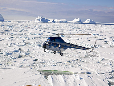 Helicopter landing on the Capt. Khlebnikov icebreaker after a flight over the icebergs off the coast of Franklin Island, Antarctica