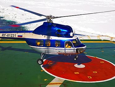 Helicopter landing on the helideck of the Captain Khlebnikov icebreaker, Antarctic