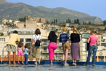 Tourists standing at deck rail, Patras harbour, Achaia, Peloponnese, Greece