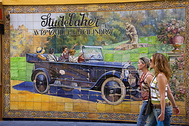 Girls passing a wall of tiles depicting a Studebaker car in Calle Tetuan street, Seville, Andalusia, Spain, Europe