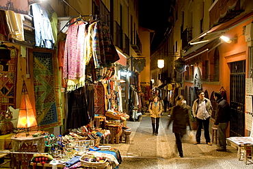 Teahouses, tourists and souvenir shops selling Moroccan handicrafts at night in the colourful Caldereria Nueva street, Granada, Andalusia, Spain