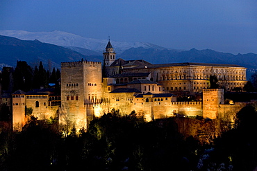 Moorish Alhambra Palace under floodlights at twilight, illuminated at dusk, Sierra Nevada at back, viewed from the Mirador San Nicolas in the El Albayzin or Albaicin quarter of Granada, Andalusia, Spain