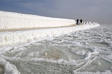 People walking on icy pier, frozen Black Sea, a rare phenomenon, last time it occured in 1977, Odessa, Ukraine, Eastern Europe