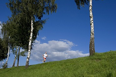 Running woman on a dam in front of blue sky