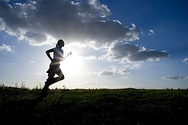 Running woman as a silhouette in front of a sky in back light