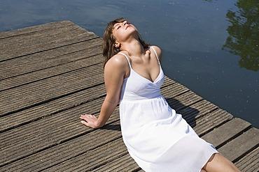 Woman in a white dress sitting on a boardwalk enjoying the sun