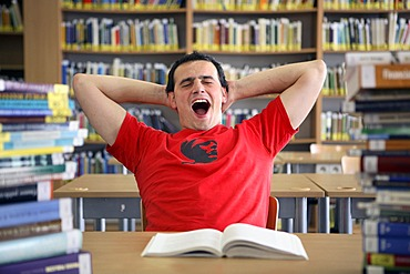 Student yawning and being lazy in a university library