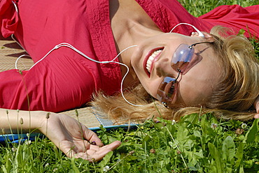 Young woman relaxing with an ipod mp3 player, listening to music