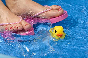 Feet wearing flip-flops in a paddling pool with a rubber duck
