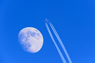 Passenger aircraft with jet trail and moon
