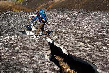 Female hiker walking on a snow slab, on the Laugavegur hiking trail, Hrafntinnusker-Álftavatn, Fjallabak Nature Reserve, Highlands of Iceland, Iceland, Europe