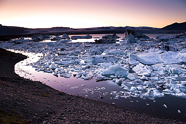 Blue and black icebergs and ice crystals in the evening light, Joekulsarlon glacial lagoon, Vatnajoekull glacier, Austurland, eastern Iceland, Iceland, Europe