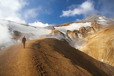 Hiker on a trail, hot springs and snow-capped Rhyolite Mountains, Hveradallir high temperature region, Kerlingarfjoell, highlands, Iceland, Europe
