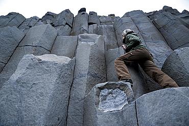 Woman climbing on basalt columns, Halsanefshellir cave, Reynisfjara beach at Vik i Myrdal, South Coast, Iceland, Europe
