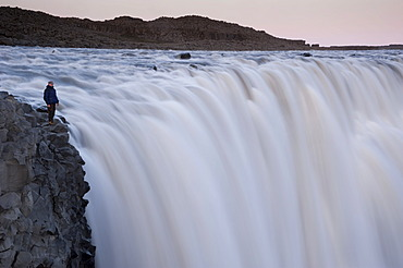 Man standing at the Dettifoss waterfall on the Joekuls√° √° Fjoellum river, Nor√∞urland eystra region, or north-east region, Iceland, Europe