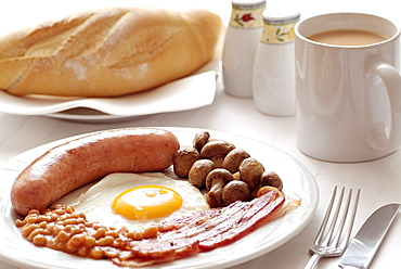 Traditional English Fried Breakfast of Sausage, Egg, Bacon, Mushrooms and Beans. Served with a Mug of Tea.
