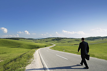 Businessman walking along a lonely country road, rear view