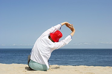 Woman wearing a red hat relaxing and stretching on the beach, Sylt island, Schleswig-Holstein, Germany, Europe