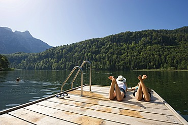 Young women lying on a landing stage on Lake Schwansee near Fuessen, Allgaeu region, Bavaria, Germany, Europe