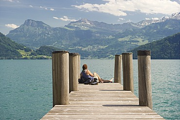 Woman sitting on a pier, hiking boots standing next to her, lakeside promenade, Weggis, Lake Lucerne, canton of Lucerne, Switzerland, Europe