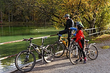 Father and children riding mountain bikes, at Badersee lake in Grainau, Werdenfelser Land, Upper Bavaria, Bavaria, Germany, Europe