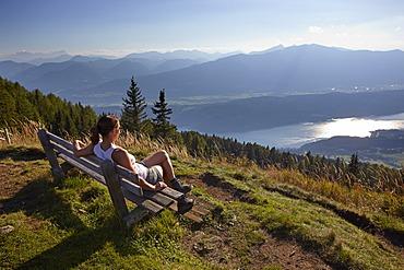 Female hiker overlooking Lake Millstatt, Carinthia, Austria