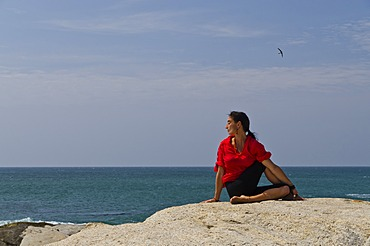 Woman in a yoga position, Ardha Matsyendrasana, by the sea in Kanyakumari, Tamil Nadu, India, Asia