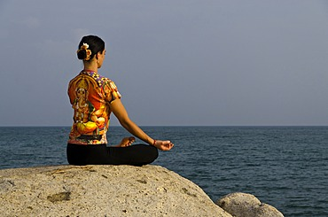 Woman in a yoga position, Padmasana, by the sea in Kanyakumari, Tamil Nadu, India, Asia