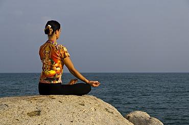 Woman in a yoga position, Padmasana, by the sea in Kanyakumari, Tamil Nadu, India, Asia