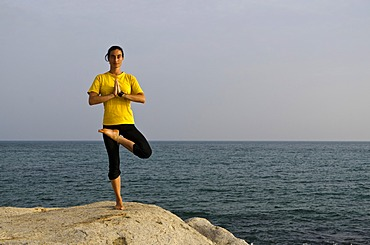 Woman in a yoga position, Vrikshasana, by the sea in Kanyakumari, Tamil Nadu, India, Asia
