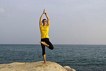 Woman in a yoga position, Vrikshasana, by the sea in Kanyakumari, Tamil Nadu, India, Asia