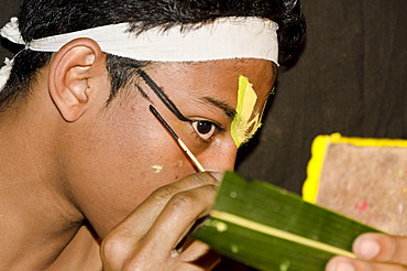 The make-up of the Kathakali character Krishna is being applied, Perattil, Kerala, India, Asia