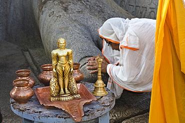 Jain pilgrim is praying at the feet of the gigantic statue of Gomateshwara in Sravanabelagola, Karnataka, India, Asia