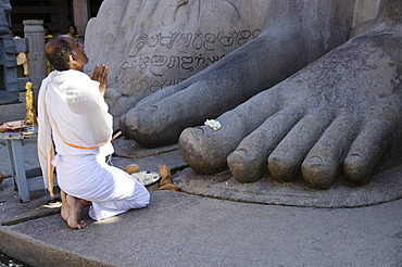 Local priest is doing his prayers in front of the gigantic statue of Gomateshwara, Sravanabelagola, Karnataka, India, Asia