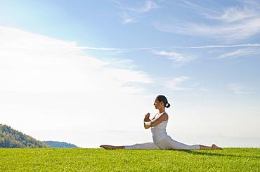 Young woman practising Hatha yoga outdoors, showing the pose anjaneyasana, hanumanasana, split, Nove Mesto, Okres Teplice, Czech Republic, Europe