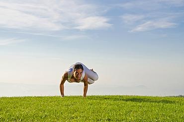 Young woman practising Hatha yoga outdoors, showing the pose parshva kakasana, parshva bakasana, sideward crow pose, sideward crane pose, Nove Mesto, Okres Teplice, Czech Republic, Europe