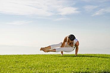 Young woman practising Hatha yoga outdoors, showing the pose kakasana, bakasana, dvi-pada-koundinyasana, variation of crow pose, Nove Mesto, Okres Teplice, Czech Republic, Europe
