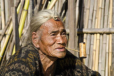 Old Apatani man with the typical hair knot at the forehead, in front of his house, Hong village, Arunachal Pradesh, India, Asia